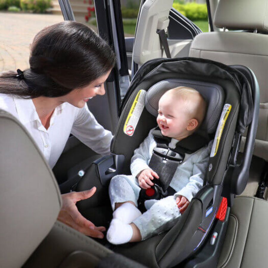 Mother placing child in car seat